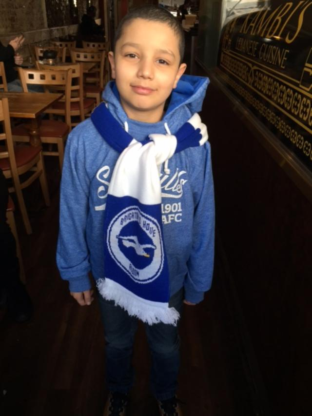 Daneal, a 8 year old boy, stands in a blue hoodie with a Brighton and Hove scarf