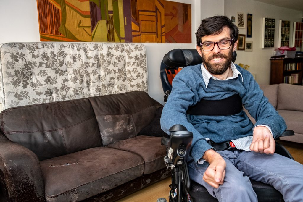 Jacob, a white man in his thirties, seated in a wheelchair in his living room
