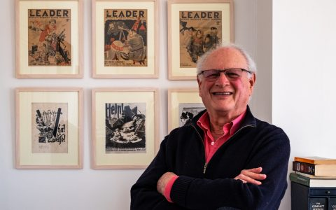 Paul, a white man with receding white hair, with an array of framed images from the Second World War, on the wall behind him