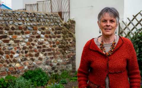 Sue, a white woman with short grey hair, standing in her garden