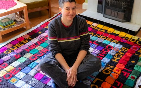 Dani, a white woman with short black hair, sitting on a colourful blanket in her living room