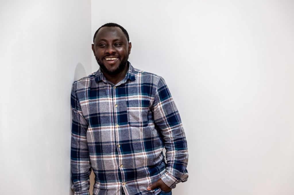 Luqman, a black man in his thirties, leaning on a white wall and smiling