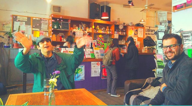 interior photo from the Jollof Cafe at the Cowley Club: two Middle-Eastern men sitting together at a table and and smiling, two other people in the background buying something at the counter
