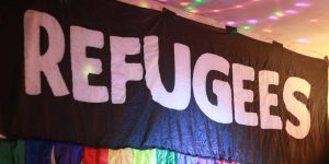 A black banner with large white letters spelling 'refugees'. The banner has a rainbow fringe