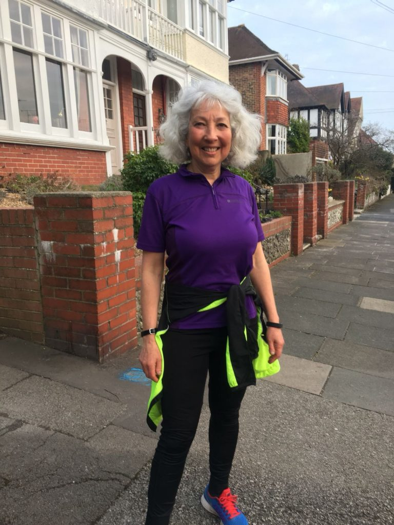 Karen, a woman in her 60s, stands in her purple and black running gear on a residential street
