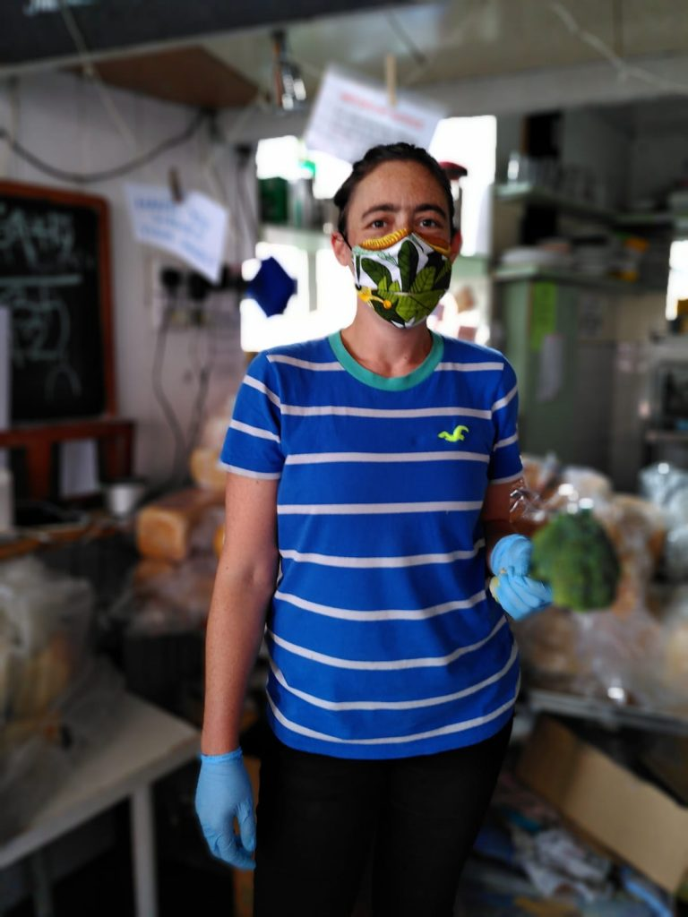 A white woman in her thirties holds a brocolli and wears one or our masks. The mask has a leaf pattern design